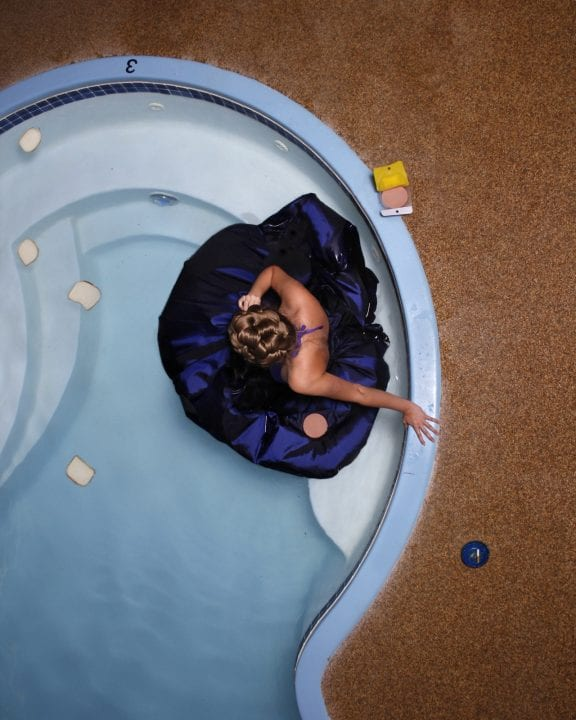 woman in blue bathtub photography of patterns from above by Hayley Eichenbaum and Zach Swearingen
