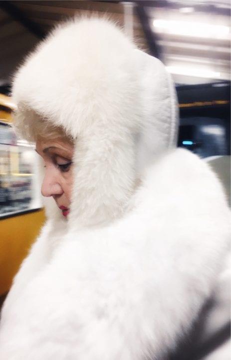 woman wearing white fur street photography of a person, by efi logginou