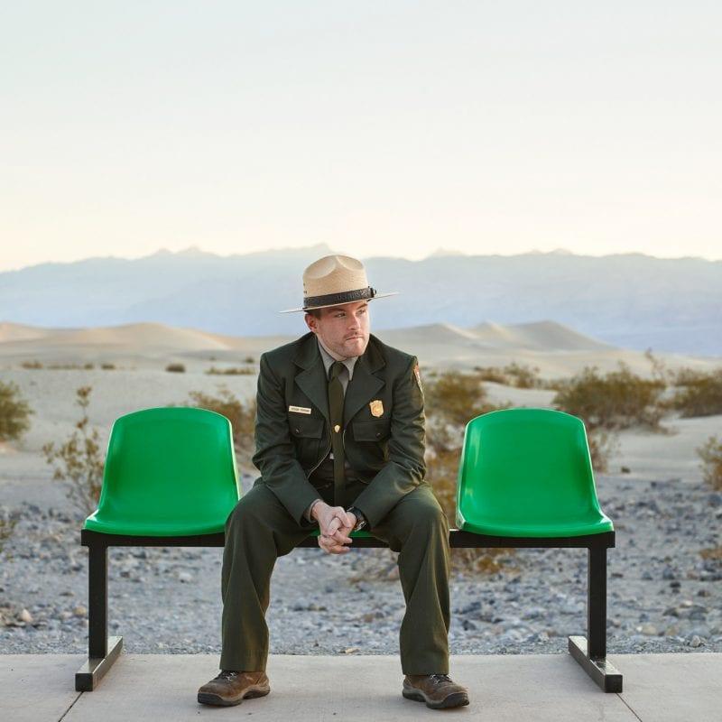男子戴着帽子,坐在绿色的长椅上,迪伦·彩色的肖像摄影