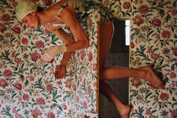 Farbfotografie, Frau vor einer blumigen Tapete
