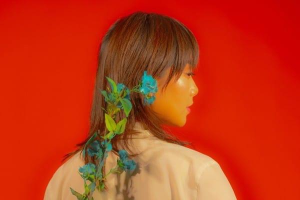 Farbfotografie, Frau mit Blume auf einem roten Hintergrund