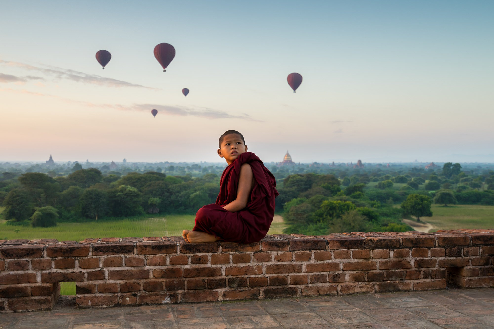 A young Buddhist monk is looking at hot air balloons taking off at sunrise