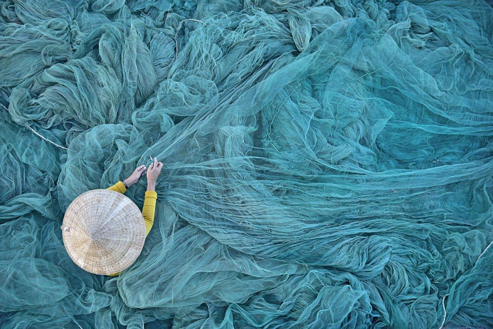 Reparieren von Fischernetzen in Vietnam