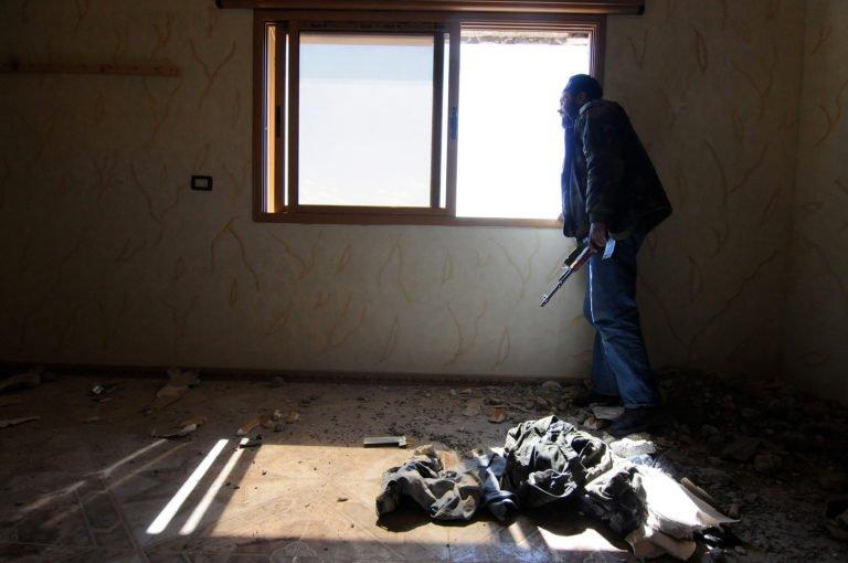 Un combattant de la FSA est à l'affût de l'intérieur d'une position défensive après que les forces gouvernementales viennent de bombarder la zone avec des chars à 80 km au nord de Damas - Syrie, 25 avril 2013, par Jonathan Alpeyrie