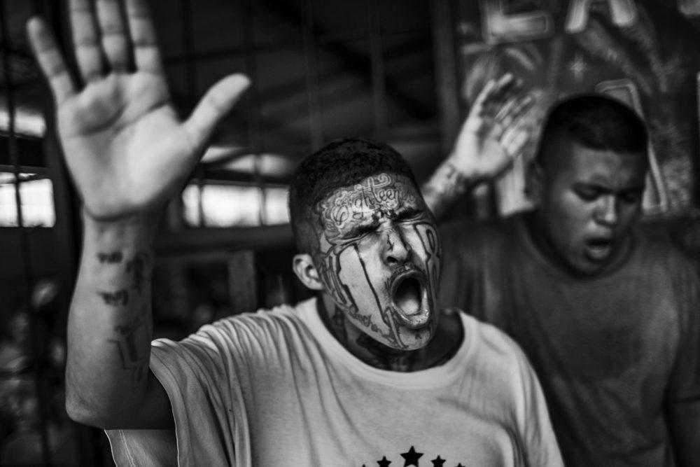 """Schwarz-Weiß-Foto von Javier Arcenillas - """"Maras Gang Member Praying"""". Gefängnis von San Francisco Gotera, El Salvador. Aus dem Langzeitprojekt 'Latidoamerika'"""