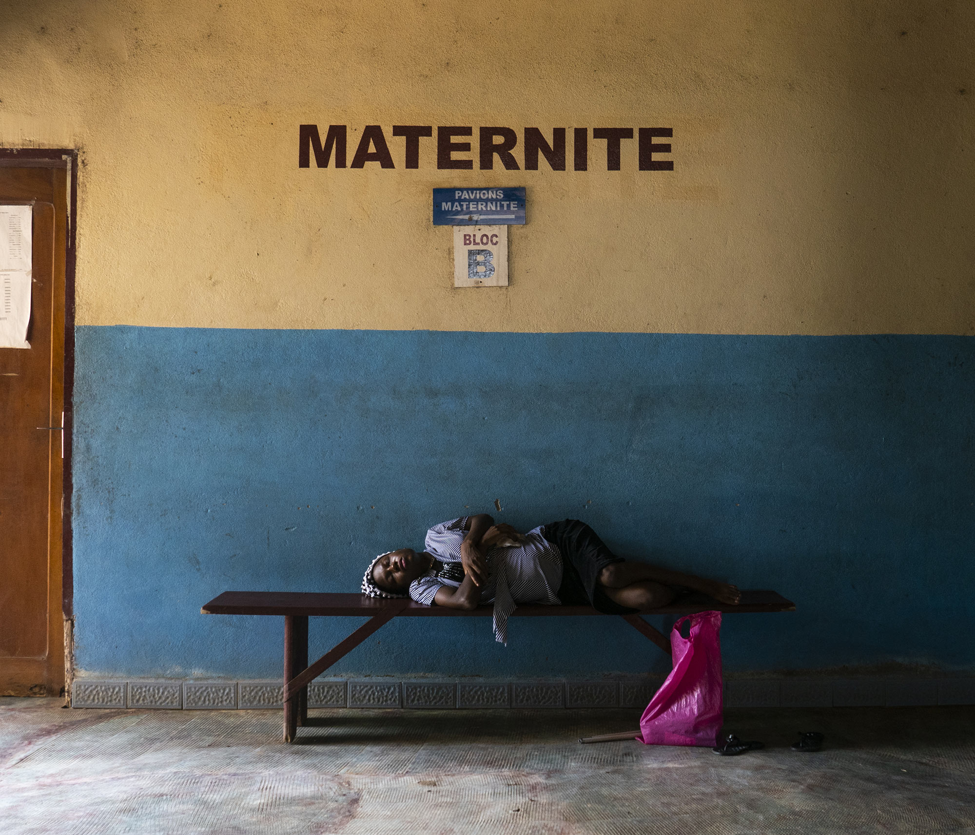 """Title: """"Madonna del parto"""" - Cameroon This portrait is part of a long-term project on the consequences of war. In this case, the civil war in Cameroon that started two years ago. Candice rests on the bench after traveling over a thousand kilometer to give birth in the hospital of Édea. The village is located near Bamenda, in the English-speaking part of the country. Due to the war between the separatists 'Amba boy' and the army, the area is under siege, the roads are almost all blocked, there are numerous checkpoints and food and drugs are in short supply. For this reason, she decided to travel for almost two days to reach a safe hospital."""
