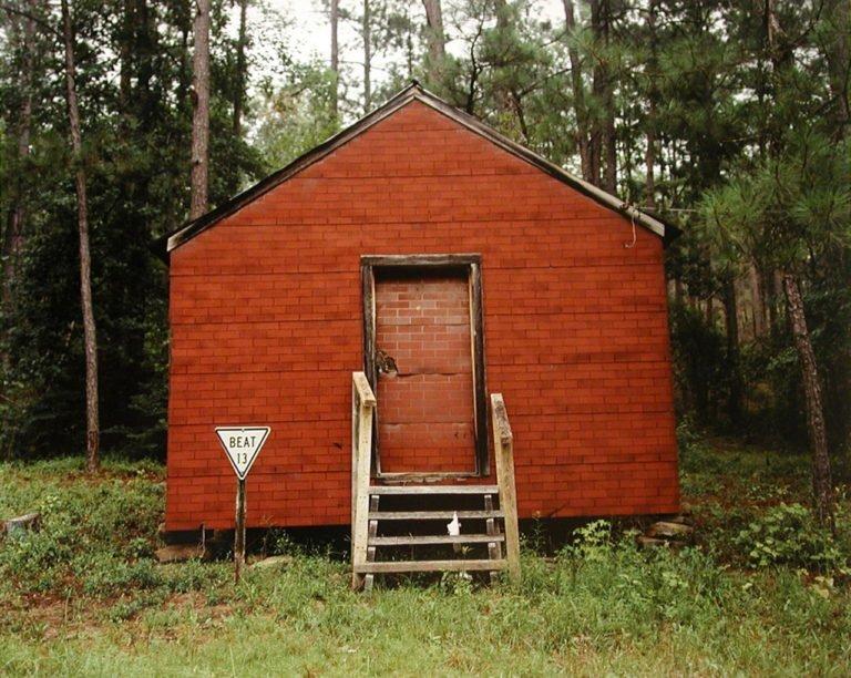 Photographie couleur, bâtiment rouge dans la forêt, comté de Hale, Alabama, 1974 © William Christenberry
