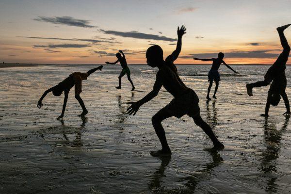 Color photograph by Steve McCurry, Madagascar, boys playing on beach, sunset, sillouhettes