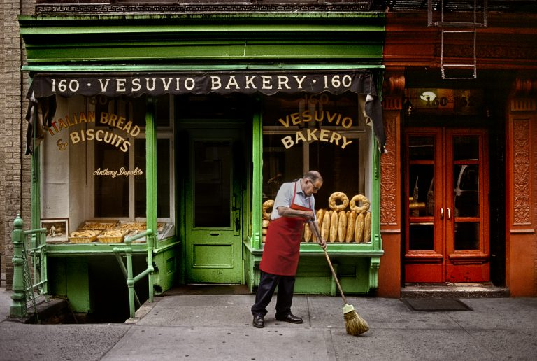 Photographie couleur par Steve McCurry, NYC, USA, homme balayant la rue devant une boulangerie italienne.