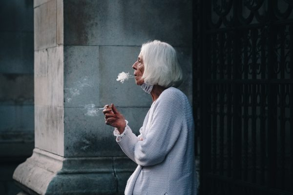 Offenes Porträt einer Frau, die in den Straßen von Holborn, London, UK 2020 raucht
