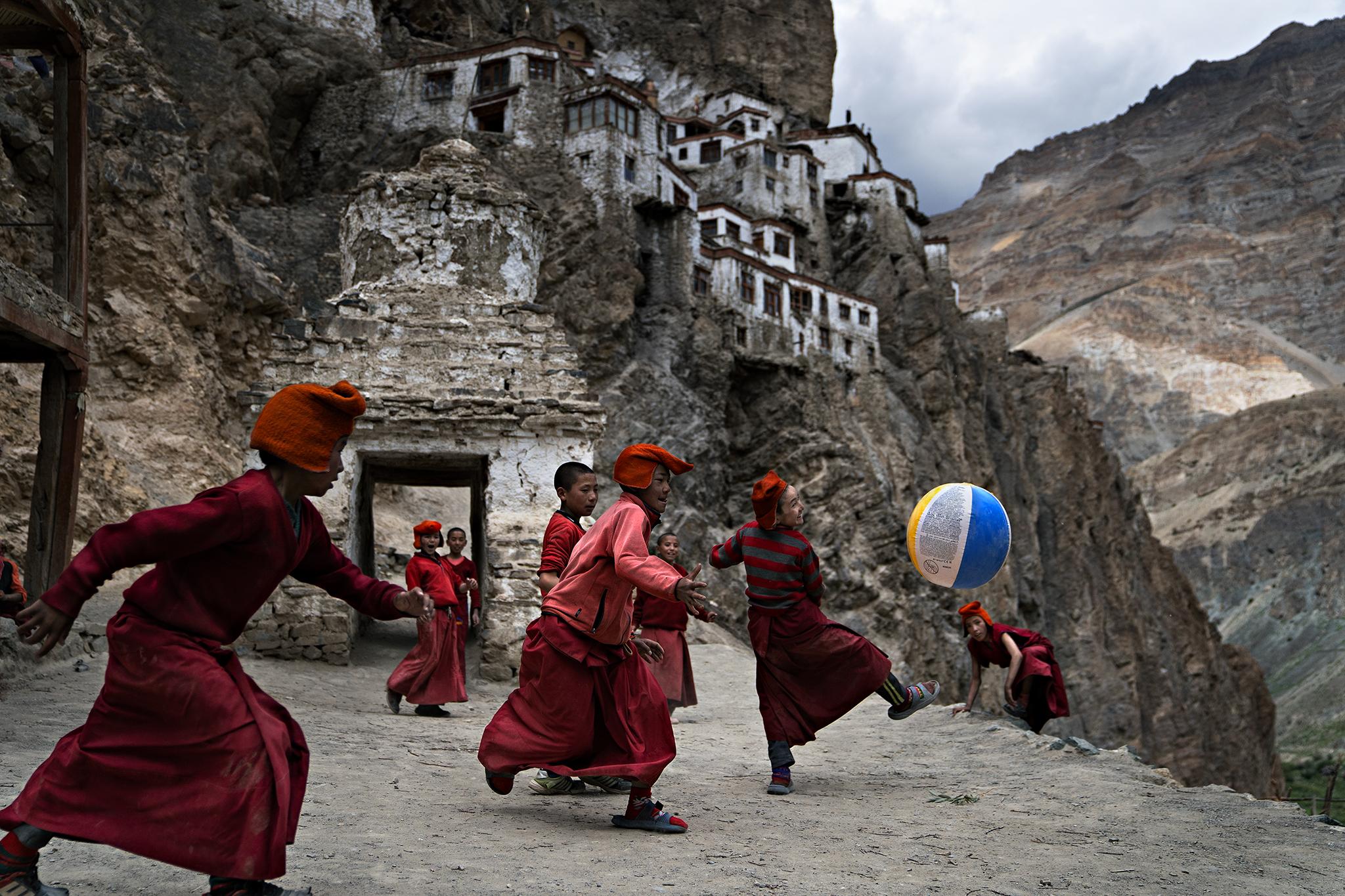Fotografia a colori di giovani monaci tibetani che giocano a calcio nel monastero di Phugtal, India settentrionale