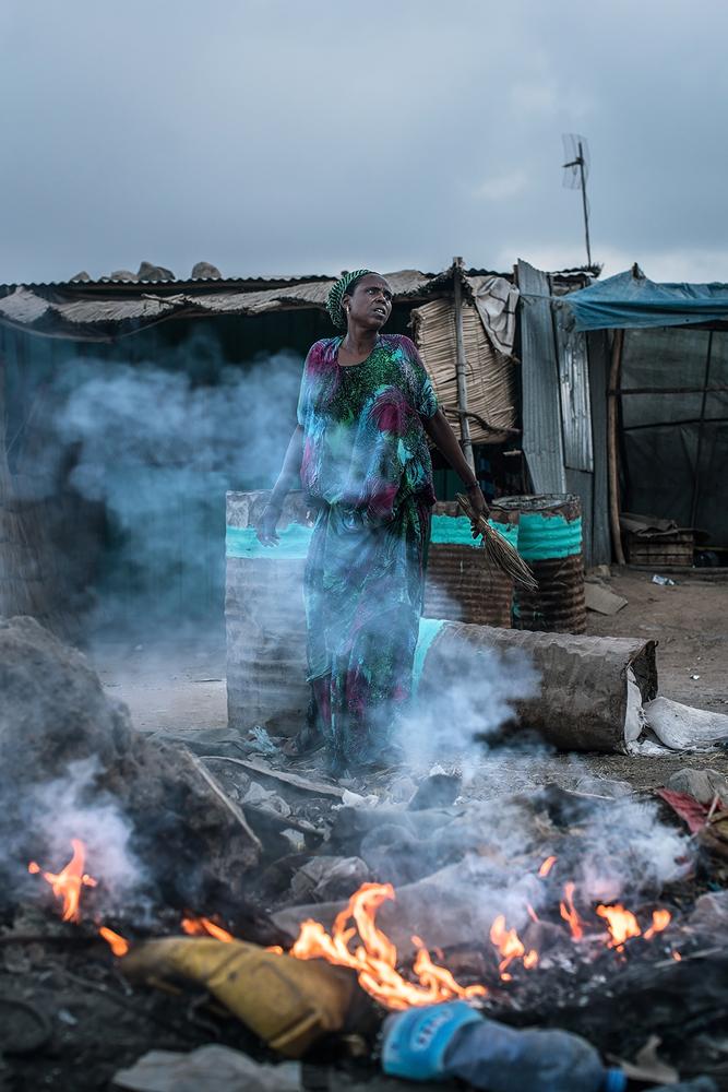 Fotografía en color por Nichole Sobecki, mujer, fuego, Djibouti, África