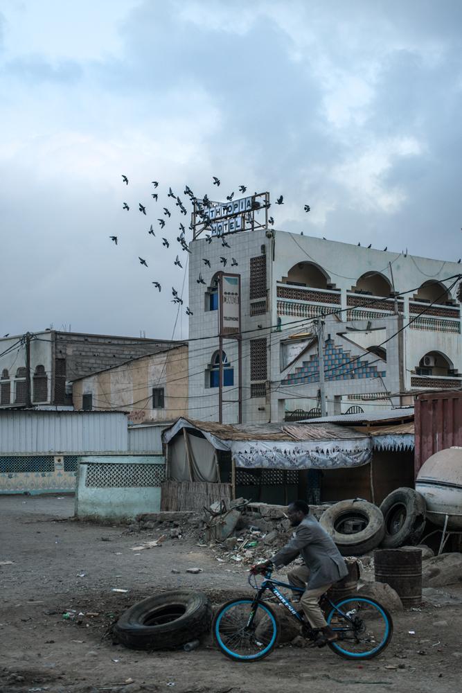 Fotografía en color por Nichole Sobecki, hombre en bicicleta, pájaros, Djibouti, África