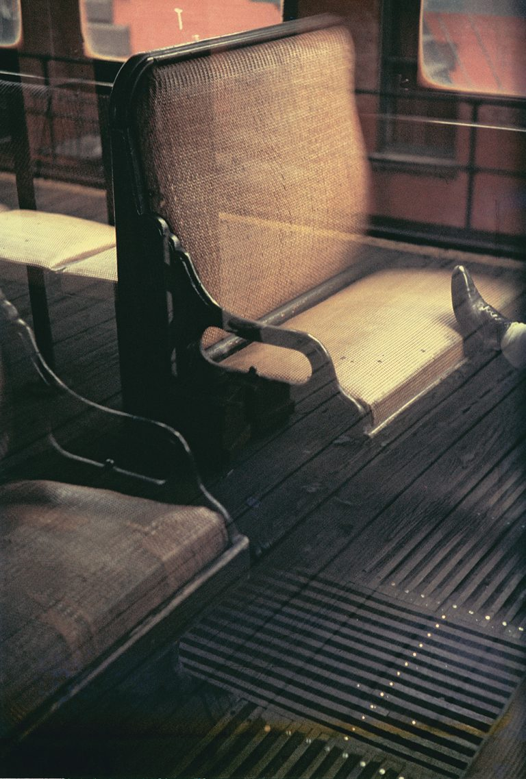 Color photo by Saul Leiter, windows, reflection foot on bus seats