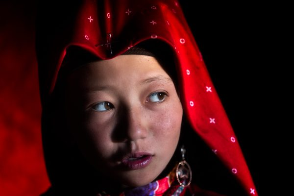 Color portrait photograph of a young kirghiz girl in red dress in Kyrgyzstan - Visual Storytelling Award