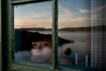 color portrait of a young boy with sky reflection by Junko Akita