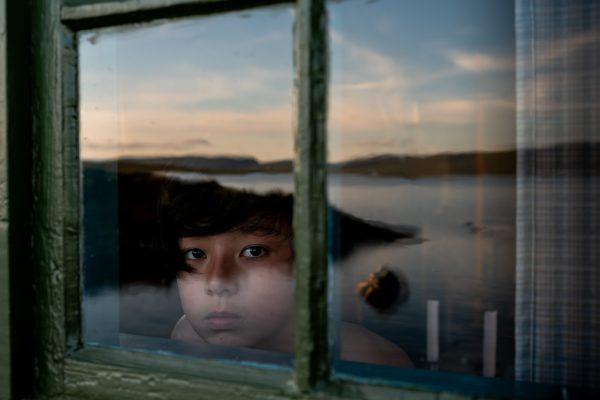 ritratto a colori di un ragazzo con il riflesso del cielo di Junko Akita