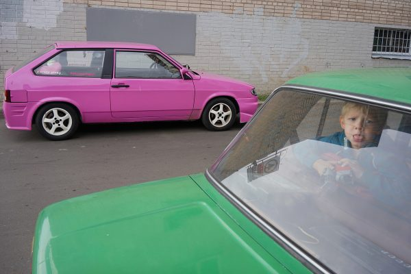 color street photography of pink and green cars and child in Saint Petersburg, Russia by Alexander Sharr