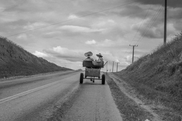 Black and white photo by Xavier Roy, 2 old men in sombrero hats riding a horse and cart, Cuba