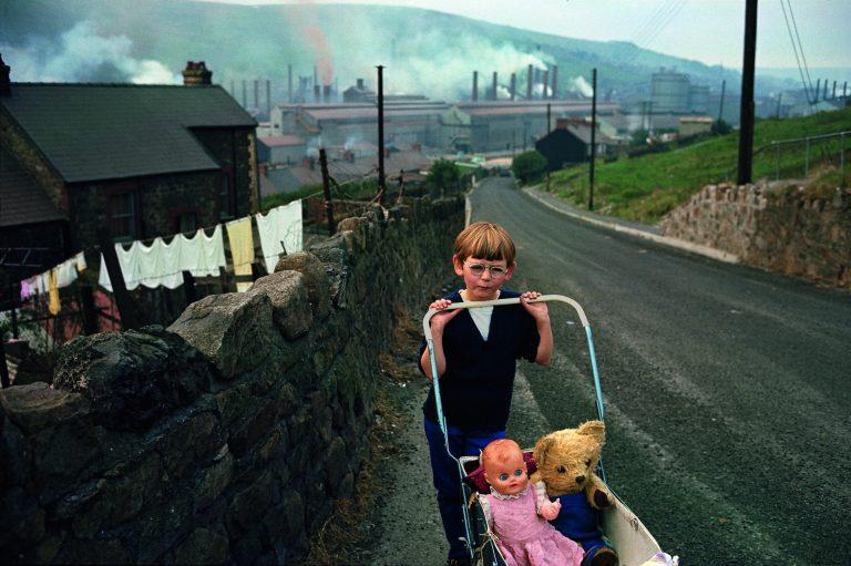 Fotografía en color por Bruce Davidson, Gales del Sur, comunidad minera, retrato de niño con cochecito
