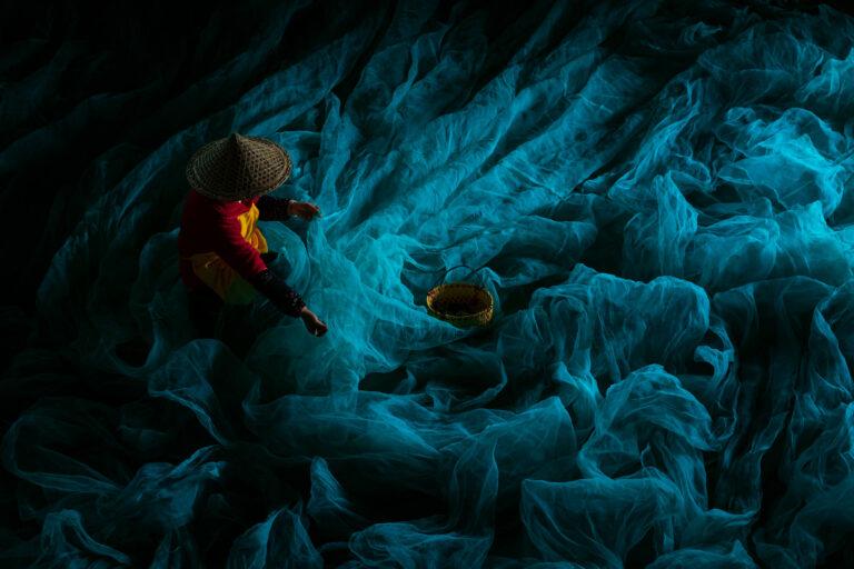 farbenfrohes Porträt eines chinesischen Fischers, der Netze repariert von Alex Berger