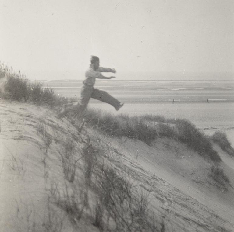 柯蒂斯·莫法特的黑白照片。 快照,人从沙丘上跳下来 c. 1925 - 1930