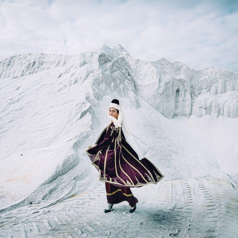 Photo couleur de Michael Pappas de la série Mitos - le fil de Grèce, femme, costume traditionnel, montagnes blanches, falaises, paysage, portrait