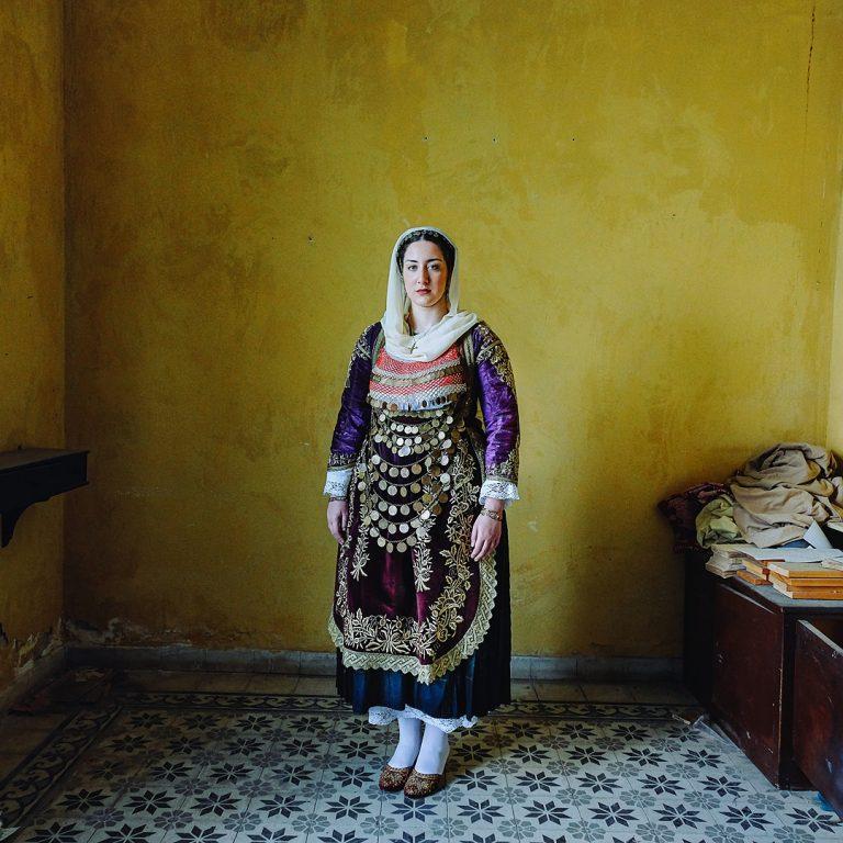 Photo couleur de Michael Pappas de la série Mitos - le fil de la Grèce, femme, costume traditionnel, maison, portrait