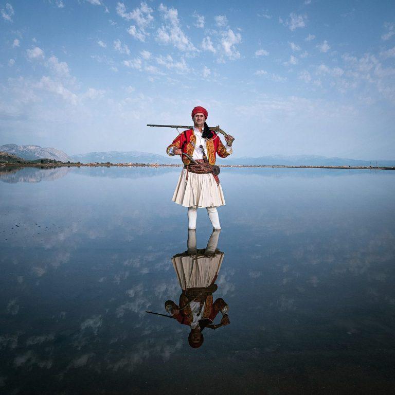 Photo couleur de Michael Pappas de Mitos - le fil de la Grèce, portrait - homme en costume traditionnel avec fusil, lac, montagnes, ciel