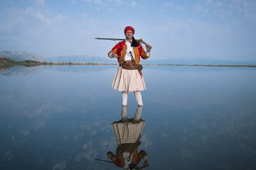 Color photo by Michael Pappas from Mitos - the thread of Greece, portrait - man in traditional costume with rifle, lake, mountains, sky
