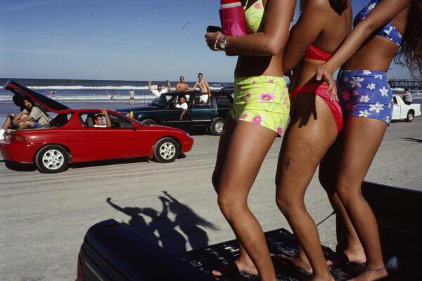 Farbfoto von Constantine Manos, Mädchen tanzen, Urlaub, Urlaub, Autos, 90er, Strand, Florida, USA