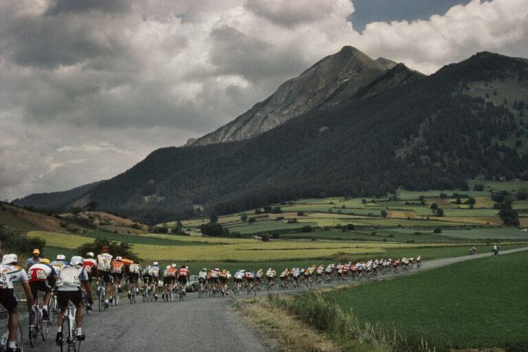 Harry Gruyaert - 环法自行车赛,1982 年 进入阿尔卑斯山脉前的山谷。 身后身穿三色球衣的是法国冠军雷吉斯克莱尔。 法国。 1982 年。